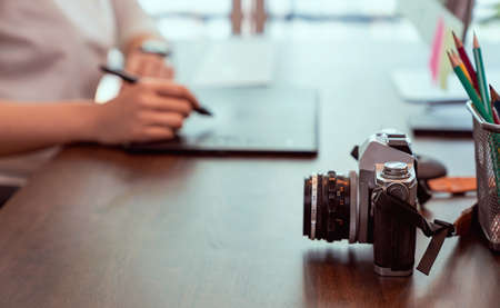 Old film camera on wood table and woman working graphic design.