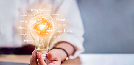 Hand holding light bulb with innovation and creativity are keys to success. Concept knowledge leads to ideas and inspiration.