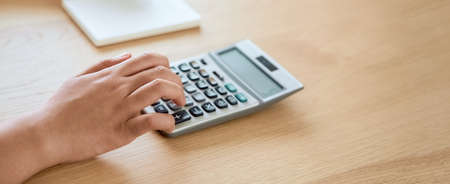 Woman press calculator to calculate income expenses and plans for spending money on home office. Stock Photo