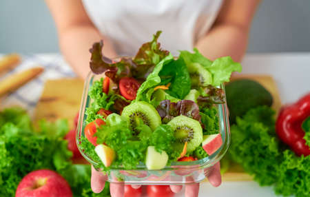 Close-up of woman hands showing salad bowl and various green leafy vegetables on the table at the home.