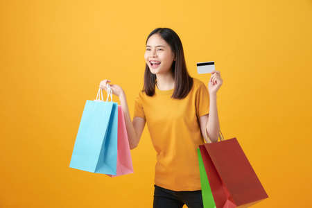 Cheerful beautiful Asian woman holding multi coloured shopping bags and credit card on light yellow background. 版權商用圖片