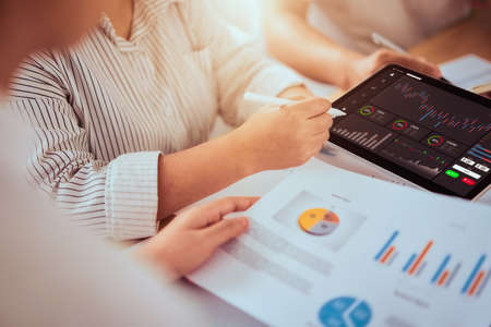 Stock exchange market concept, businessman trader and team looking on tablet with graphs analysis candle line in office room, diagrams on screen. Stock Photo