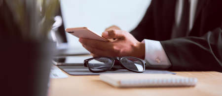 Hand of businessman in a black suit using smartphone on wooden table with typing message to contact customer and eye glasses. 版權商用圖片