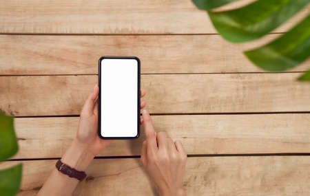 Woman hand holding a smartphone and pressing blank screen on wood table, take your advertising. Technology for communication concept.