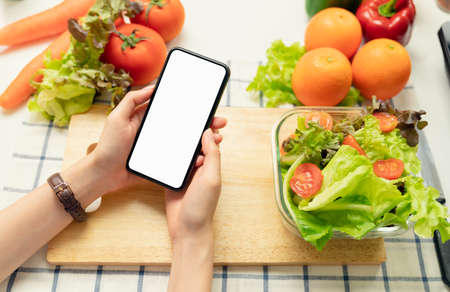 Woman hand holding a smartphone blank screen and salad bowl with tomato and various green leafy vegetables on the table at the home, take your advertising.