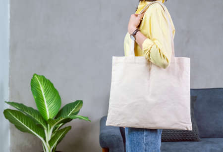 Woman in casual yellow t-shirt stand and holding bag canvas fabric for mockup logo.