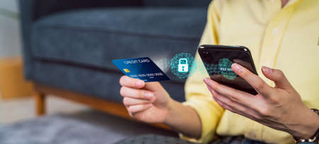 Woman holding smartphone and credit card with scanning biometric fingerprint for approval to access for payment mobile banking on application wallet. Stock fotó