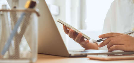 Close-up of hands holding pen and writing on notepad with learning online course from digital laptop, smartphone on desk.