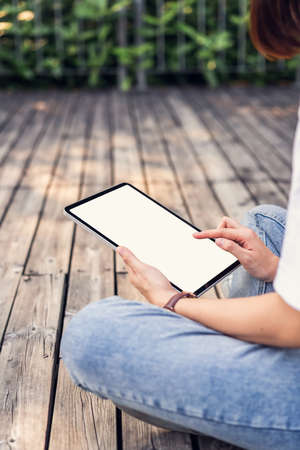 Woman hand sitting and holding digital tablet with blank screen on the park.
