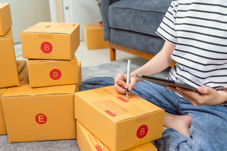 Startup small business concept, young woman owner working and packing on the box to customer at the sofa in home office, seller prepares the delivery. Stock Photo