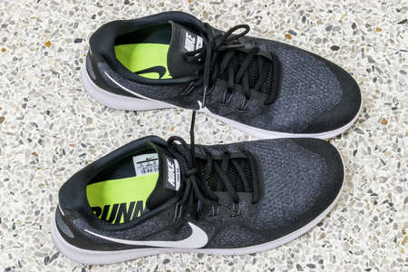 Bangkok, Thailand - January 16, 2018: View of nike shoes for running which are on the concrete floor. That is seem ready to run or jogging outside home with the greatest sport running shoe.