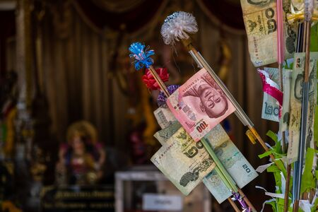 The background of Thai Baht notes decorated on the money tree for Buddhist temple donation as an offering for getting the blessing through their belief and faith of Buddhism