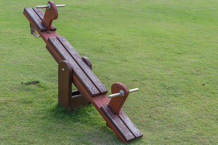 totter: Wooden Teeter totter in public playground Stock Photo