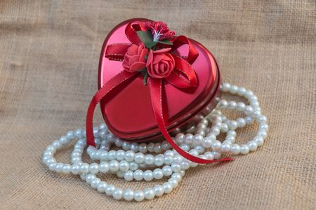 adorned: Heart-shaped box on a sack adorned with beaded necklace. Stock Photo