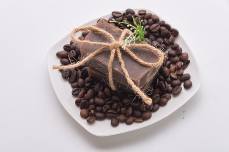 suggesting: Traditional home made natural coffee soap with a pile of coffee beans on the background suggesting healthy organic non toxic wash products