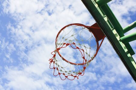 the height of a rim: Outdoor basketball hoop and blue sky