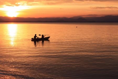 kayak: Afbeelding van silhouet, Rower bij zonsondergang Stockfoto