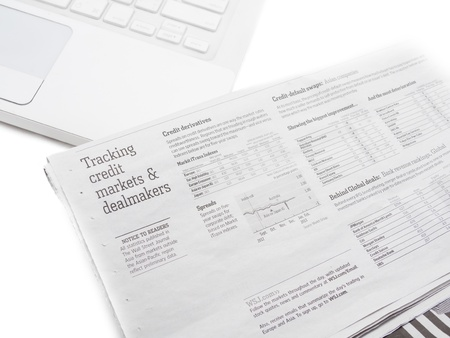 White laptop and the stock market paper  Isolated on a white background photo