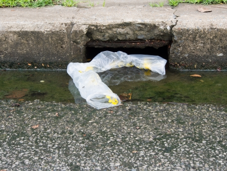 affect: Thrown plastic bags affect dirty water drains Stock Photo