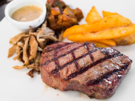 rib eye: Rib eye steak meal with french fries and mushroom