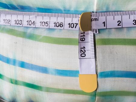 decreasing in size: concetto di dieta, tessuto con nastro di misura Archivio Fotografico