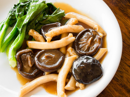 Eringii And Shiitake Mushroom in red sauce served with kale