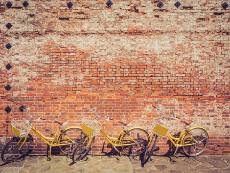 Three yellow bicycle against a brick wall with a retro and vintage filter effect photo
