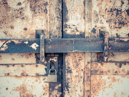 Old rusty grunge iron gate and padlock with a retro and vintage filter effect photo