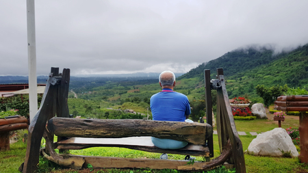 gerontology: Old man sitting alone on wooden bench,Old Lonely Man Sitting Alone,Mountains with fog in the morning. Stock Photo