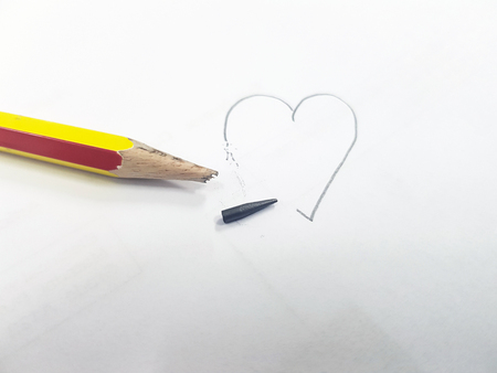Sharpened pencil over a blank old sheet of paper with a broken tip,Drawing a heart not complete.