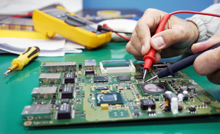 Maintenance support and repairing service concept. Electronic circuit board inspecting close up. Engineer measuring computer component Stock Photo
