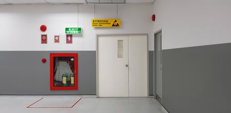 Fire exit way door and fire exit sign lightbox and fire hose in electronic industry ,Green emergency exit sign door direction in case of emergency signage,Fire safety symbol and fire protection.