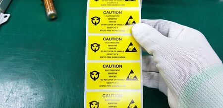 Hand holding ESD symbol label with antistatic gloves,Electrostatic Sensitive Devices (ESD) in electronic industrial.