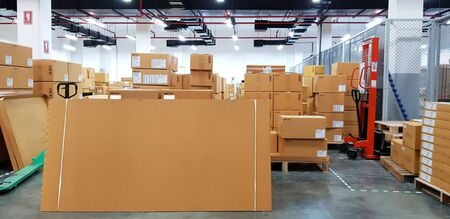 Paper board empty on blurred background. Perspective brown paper over blur in large warehouse logistic or distribution center,Can be used mock up for montage products display or design.