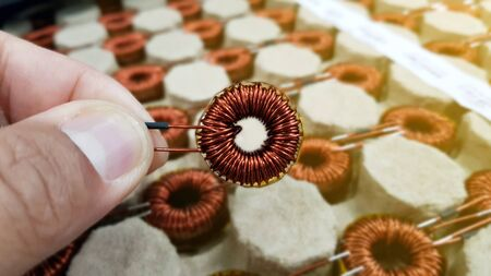 Transformer coil in hand,Toroidal Coil Inductor,Copper wire winding, Magnetic ferrite core,Electromagnetic coil, inductor on circuit board close-up Banque d'images