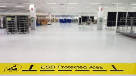 """Su un pavimento della produzione di elettronica, il linoleum industriale coperto incolla un nastro giallo con un testo di avviso standard: """"Area protetta ESD"""", sfondo sfocato, spazio per la copia"""