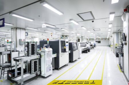 On a floor of the electronics manufacturing covered industrial linoleum pastes a yellow tape with a standard warning text: