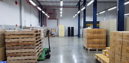 Industrial Warehouse interior with pallets of cardbord boxes and document cabinet.