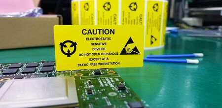 The yellow CAUTION label for Electrostatic Sensitive Devices (ESD) on static free workstation. Фото со стока