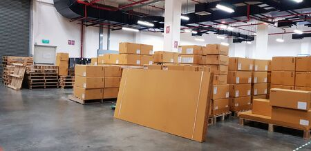 Large warehouse logistic or distribution center. Interior of warehouse with rows of shelves with big boxes.