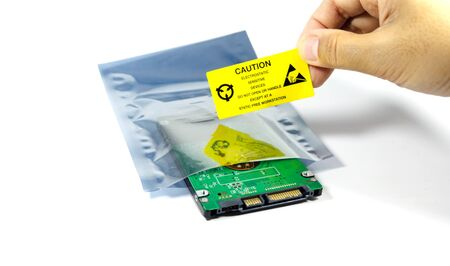 Hands of the engineers who are labeling the ESD protection label on the bag,The yellow CAUTION label for Electrostatic Sensitive Devices (ESD) on static free workstation.