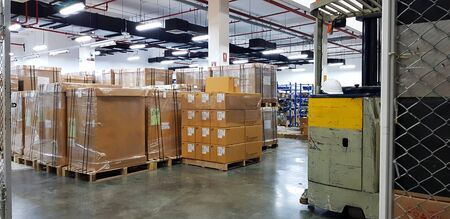 Forklift truck with a Safety Helmets (Head Protection) at large warehouse logistic or distribution center. Interior of warehouse with rows of shelves with big boxes.