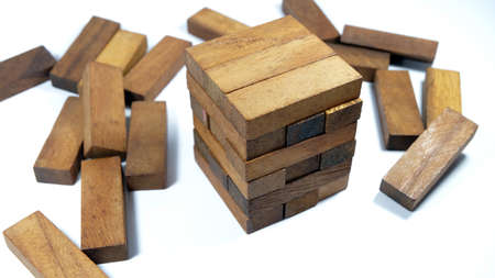 Images of hand of businesspeople placing and pulling wood block on the tower Alternative risk concept plan and strategy in business Risk To Make Business Growth Concept With Wooden Blocks.