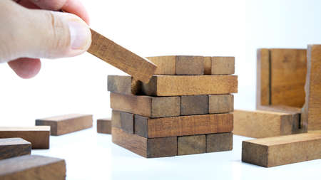 Images of hand of businesspeople placing and pulling wood block on the tower Alternative risk concept plan and strategy in business Risk To Make Business Growth Concept With Wooden Blocks. 免版税图像
