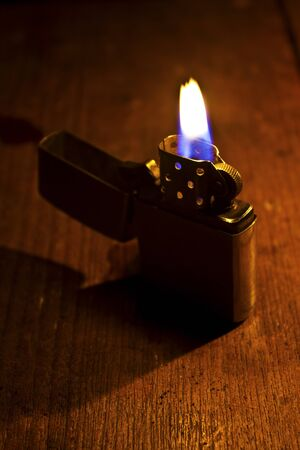 Burning lighter on dark background photo