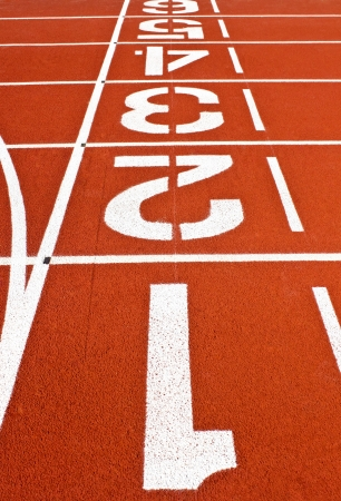 Starting line on a red running track at stadium Stock Photo