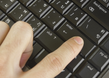 Finger pushing the button of keyboard computer photo