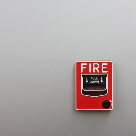 ring of fire: fire alarm on wall background