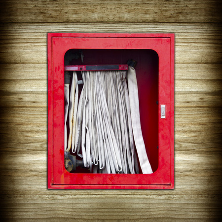 The old red fire hose cabinet on wood background