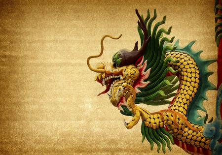 Dragon statue on old paper background photo